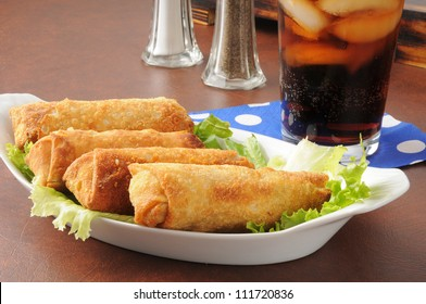 A plate of egg rolls with cola or root beer