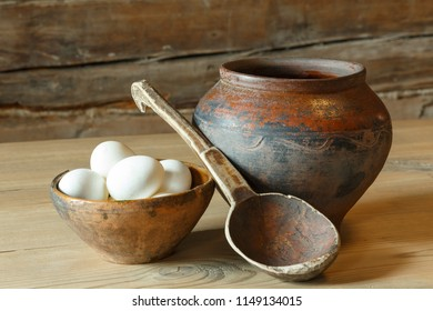 A plate of eggs, a pot and a wooden spoon.