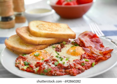 Plate with eggs in purgatory on table