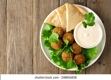 Plate of falafel with pita bread and tzatziki sauce on wooden table. View from above