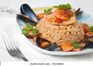 A plate of fancy italian risotto alla pescatora with seafood and fresh parsley