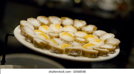 """A plate of a Filipino rice dessert cakes, called """"puto"""" and the darker """"kutsinta"""""""
