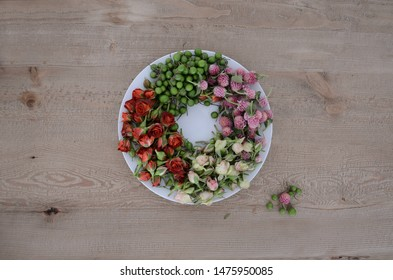 A plate filled with fresh flowers and tiny roses on a wodden table in Goiania, Goias, Brazil