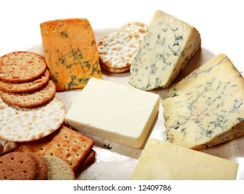 A plate of fine English cheeses with an assortment of biscuits. Clockwise from top left: Shropshire Blue, Blue Stilton, Wensleydale blue, mature cheddar and white Cheshire.