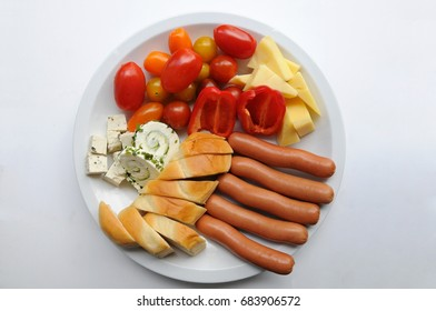 Plate with finger foods for dementia patients, who can not eat with cutlery any more - small pieces of  bread, small pepper, cherry tomato, cheese,  frankfurter sausages, tofu, spreads with chives.