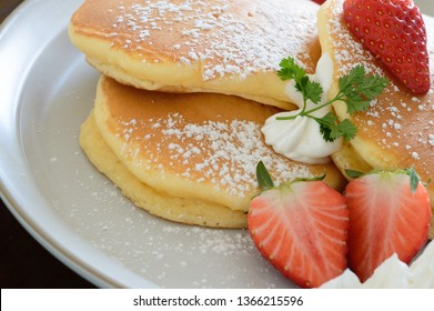 a plate of fluffy thick Japanese pancakes with strawberries