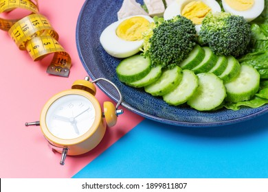 Plate with food and alarm clock on a pink and blue background