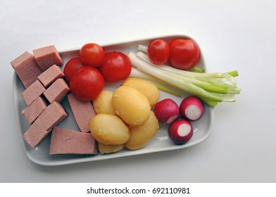Plate with food, cut in pieces for eating with fingers, suitable for dementia patients - meatloaf, small potato, cherry tomato, radishes and young onion.