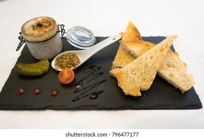 Plate of food. Starter of pate with mustard, cherry tomato, pickle, bimbo bread, on a plate of slate. Succulent food