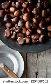 A plate of foraged chestnuts on a rustic background.
