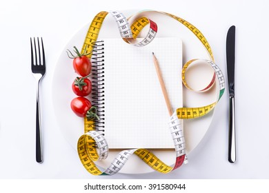 Plate, fork, knife, metering tape, pencil, tomatoes and notebook on light wooden table