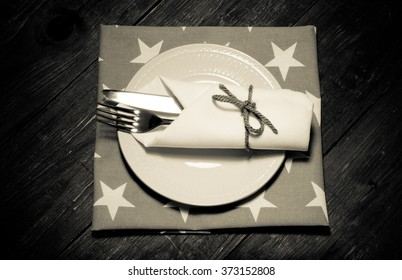 Plate, fork and knife in napkin on wooden background. Toned.