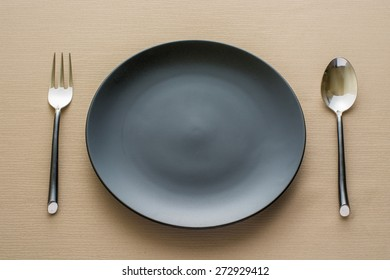 plate and fork spoon on black background.