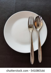 plate with fork and spoon on dark brown table