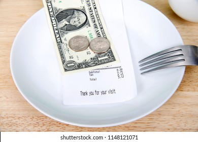 Plate with fork upside down indicating finished with meal, mug beside, bill receipt on plate. For mathematically challenged patrons, double the tip to calculate roughly how to leave for gratuity.
