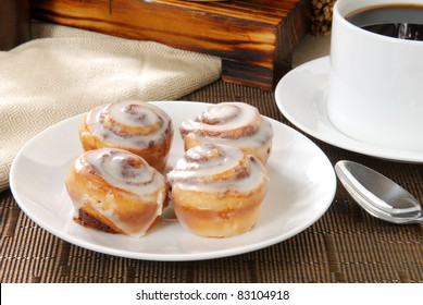 A plate with four cinnamon rolls and a cup of coffee