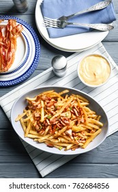 Plate with french fries and bacon on table