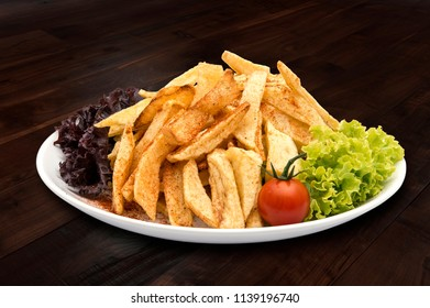 Plate of french fries with green salad, fresh red tomato and spices on white plate set on dark wooden table