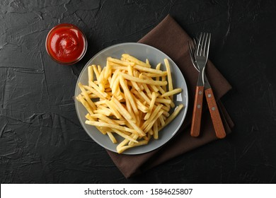Plate of french fries, napkin, red sauce, forks on black background, space for text. Top view