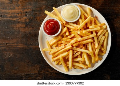 Plate of french fries potatoes served with ketchup and mayonnaise sauces in small bowls, viewed from above on dark wooden background with copy space