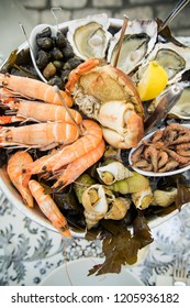Plate with fresh assorted seafood in french summer restaurant. Close up image