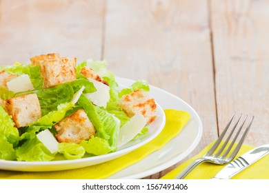 A plate with a fresh Caesar salad on a rustic table in bright light.