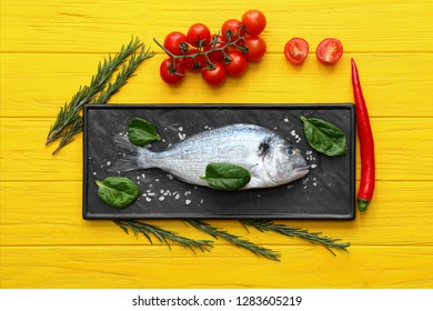 Plate with fresh dorado fish, vegetables and herbs on color wooden background