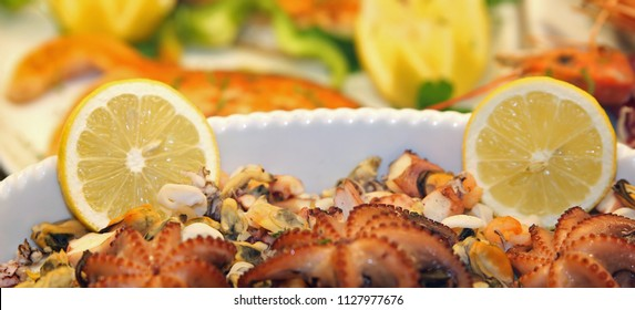plate of fresh fish topped with two slices of lemon served in a luxury restaurant