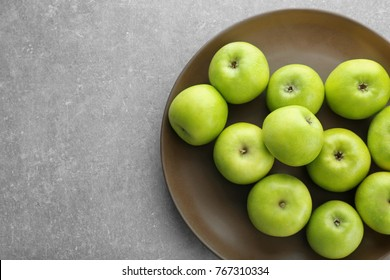 Plate with fresh green apples on grey background