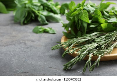 Plate with fresh green herbs on table, closeup