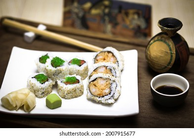 A plate with fresh, healthy gourmet maki sushi sliced rolls made of rice, raw salmon and tuna fish, expensive green caviar, sesame seeds, nori and fried tempura prawn with strong