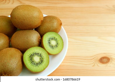 Plate of fresh kiwi fruits with the cross-sections on wooden table with copy space