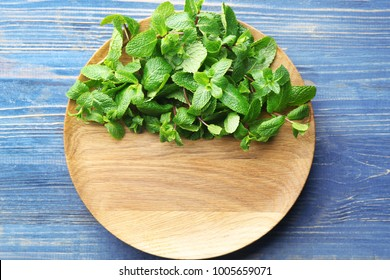 Plate with fresh lemon balm on wooden background