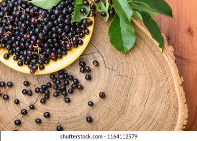 A plate of fresh maqui berries on a wooden background.
