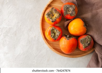 Plate of fresh and ripe persimmons. Top view and copy space.