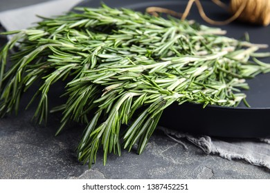 Plate with fresh rosemary twigs on table, closeup
