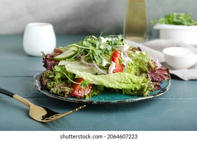 Plate of fresh salad with Lollo Rosso lettuce on table