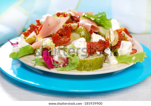 plate of fresh salad with parma ham,feta cheese and vegetables