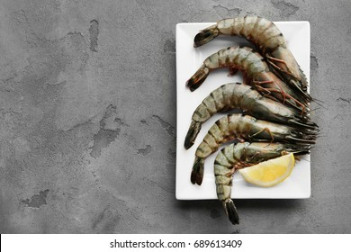Plate with fresh shrimps and lemon on grey background