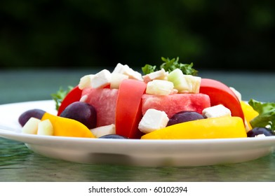 Plate of fresh summer salad with tomatoes, watermelon, bell peppers, grapes, feta cheese and cucumber