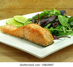 plate of freshly fried salmon fillet with baby greens