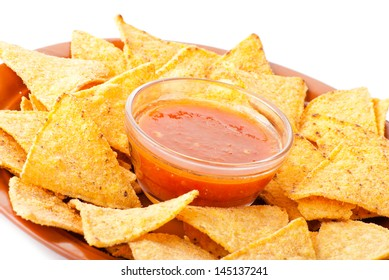 Plate of freshly made spicy nachos with tomato dip on white background