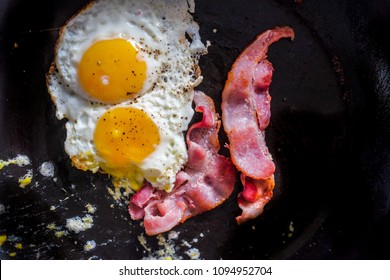 Plate with fried eggs, bacon and chicken sausage on white background