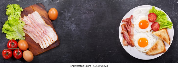 plate of fried eggs with bacon and ingredients for cooking on dark background, top view