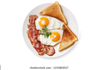 plate of fried eggs, bacon and toast isolated on white background, top view