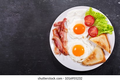 plate of fried eggs with bacon and vegetables on dark background, top view