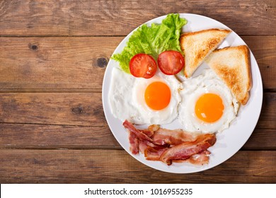 plate of fried eggs with bacon and vegetables on wooden table, top view