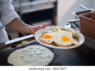 Plate with fried eggs and hand in a breakfast buffet