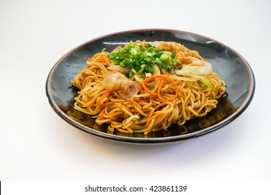 Plate of fried noodle with pork meat on white background
