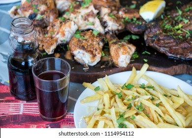 Plate with fried potatoes, red wine and tray of grilled meat in a restaurant in the north of Tenerife, Canary Islands, photo with selective focus